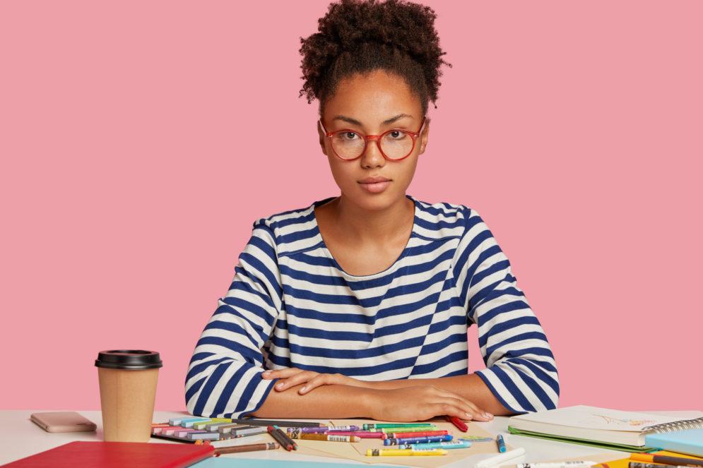Lehrerin mit Utensilien an Schreibtisch