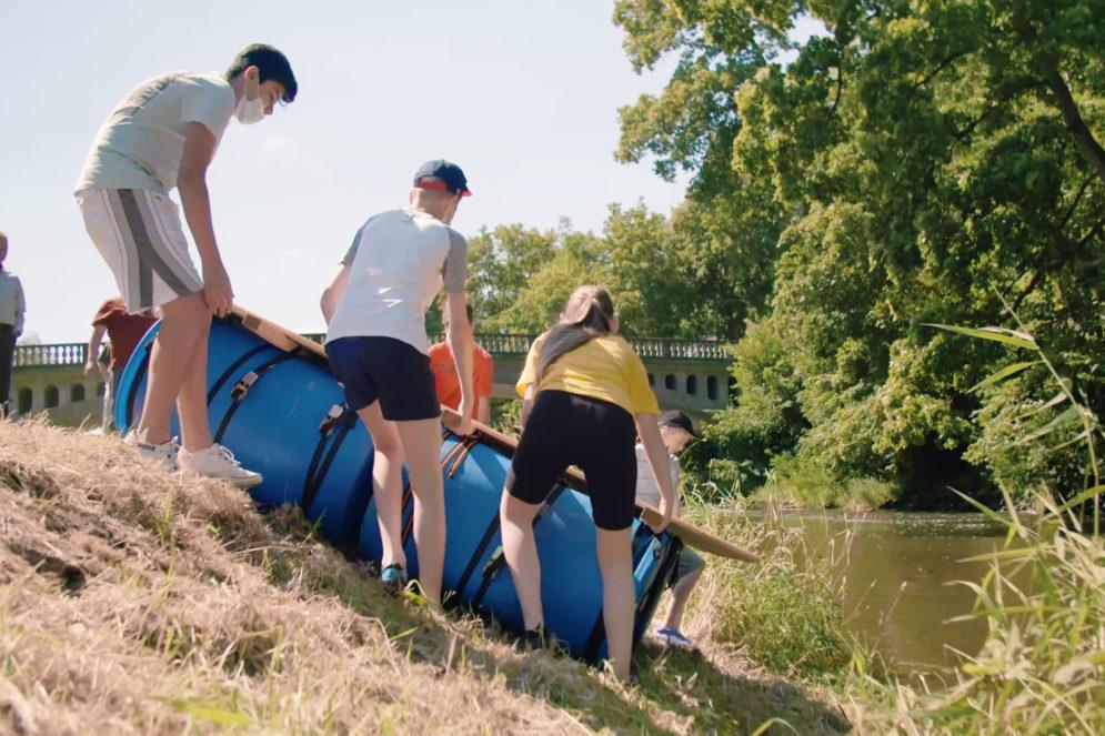 Eine Gruppe von Schülerinnen und Schülern schiebt ein Floß ins Wasser.
