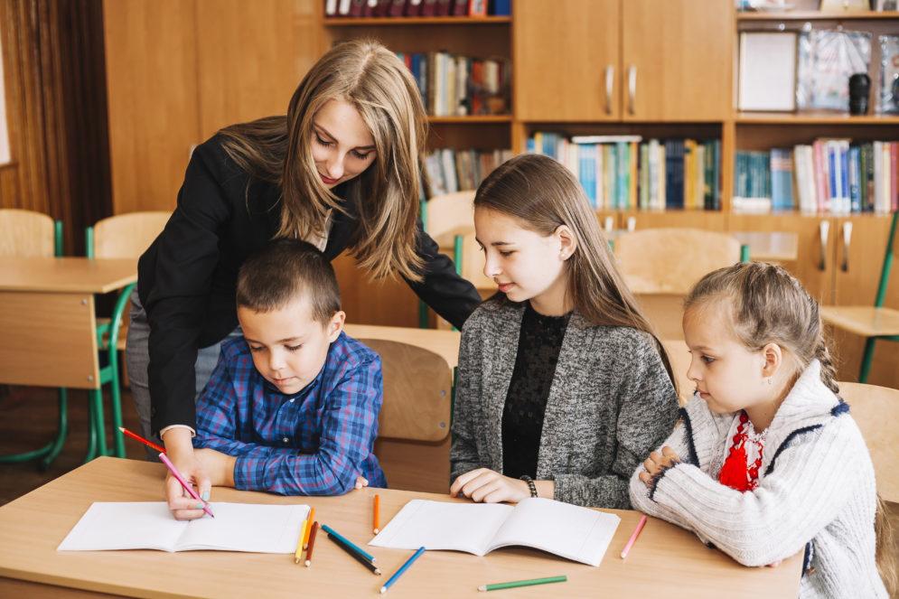 Lehrerin unterrichtet Schüler verschiedener Altersstufen