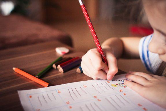 Schulkind schreibt und malt konzentriert